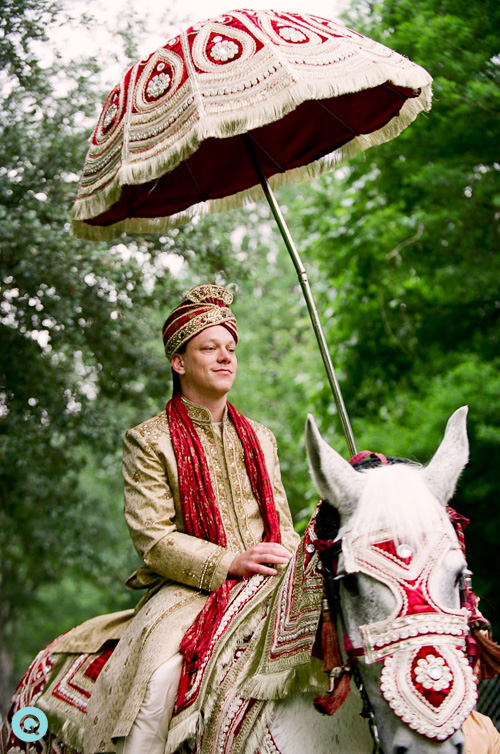 groom on white horse during baraat