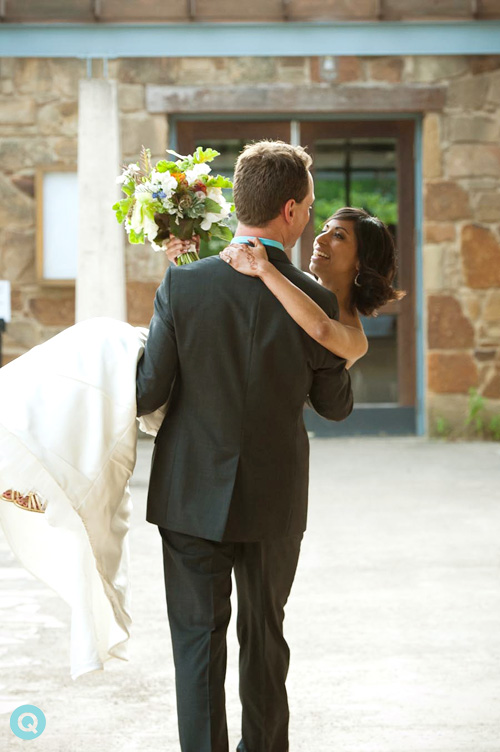 groom carrying bride over threshold
